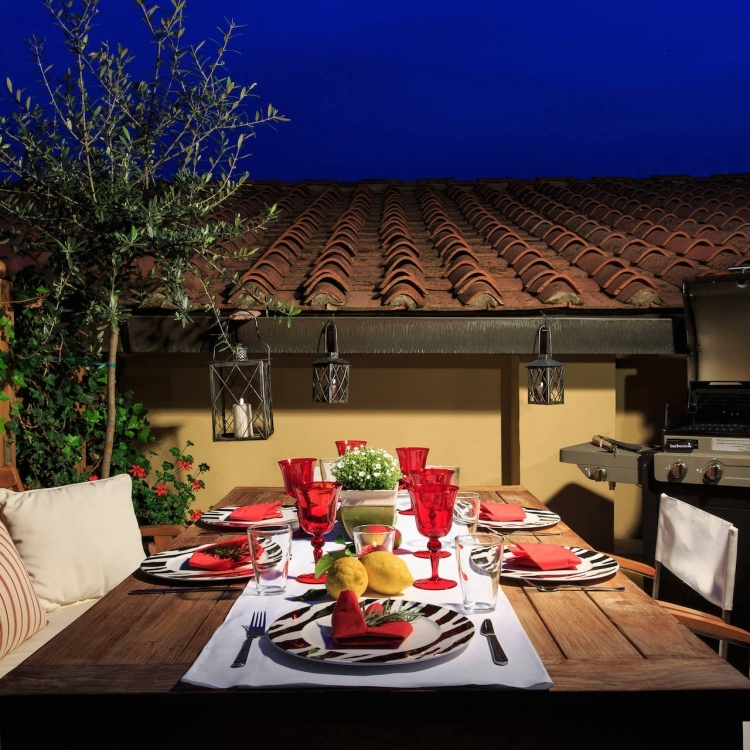 Main terrace with dining table, sun umbrella, sun beds and gas grill.