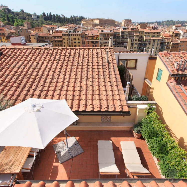 View onto the main terrace with dining table, umbrella, sun beds and gas grill.